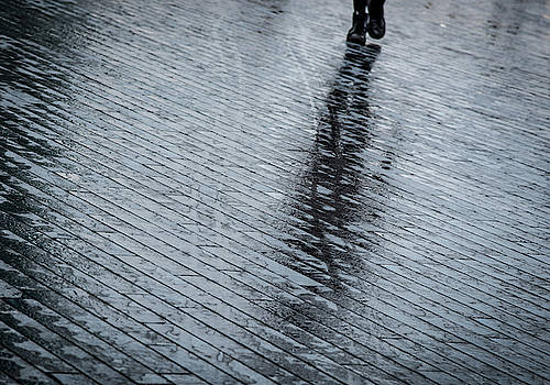 Walking shadow of an unrecognised person walking on wet streets  by Michalakis Ppalis