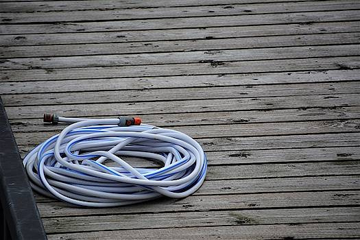 Water hose on dock by Norman Burnham
