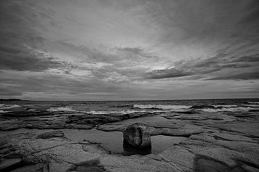 Waves are rolling towards the rocky ocean shore on a windy day - monochrome by Ulrich Kunst And Bettina Scheidulin