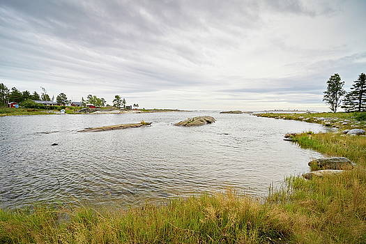 Wide angle photograph of an ocean bay with grassy shore on a cloudy day by Ulrich Kunst And Bettina Scheidulin