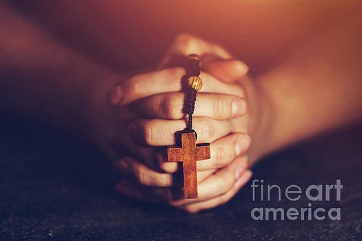 Woman holding a rosary and praying. by Michal Bednarek