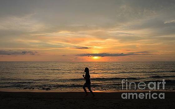 Woman running along the sunset in photograph by Christopher Shellhammer