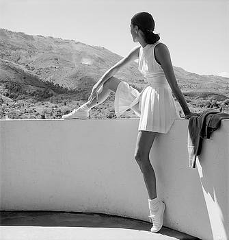 Woman Wearing Tennis Outfit Seated On Wall Looking At The Mountains by Toni Frissell