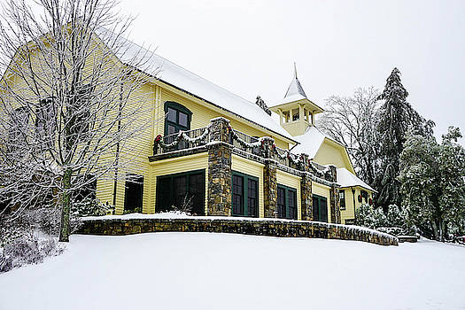 Yellow Building decorated for Christmas in the snow by Seth Solesbee