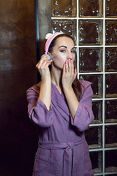 Young Girl In A Purple Robe Stands In The Bathroom And Makes A Pear Face Massage by Elena Saulich