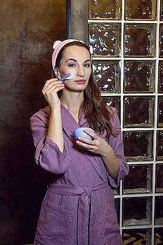 Young Girl In A Purple Robe Stands In The Bathroom And Puts Cream by Elena Saulich