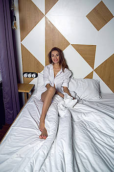 Young Girl In White Shirt Sitting On Big Bed by Elena Saulich