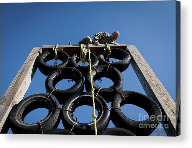 Clambering Acrylic Print featuring the photograph A Soldier Climbs Over A Tire Tower by Stocktrek Images