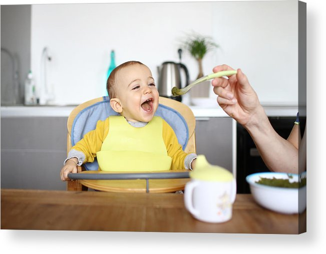 Baby Food Acrylic Print featuring the photograph A 1 year old baby boy eating in his high chair by Catherine Delahaye