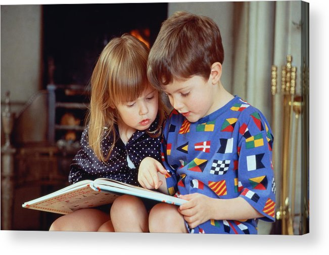 4-5 Years Acrylic Print featuring the photograph Boy(4-5)and girl(2-3)sat by fire in pyjamas reading book together by Bob Thomas