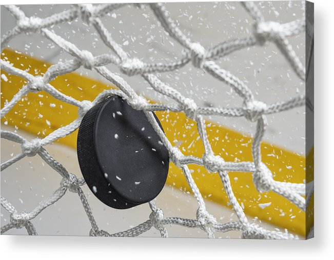 Goal Acrylic Print featuring the photograph Close-up of an Ice Hockey puck hitting the back of the net as snow flies, front view by Cmannphoto