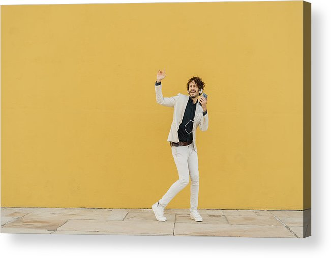 Hand Raised Acrylic Print featuring the photograph Businessman singing and dancing in front of yellow wall listening music with headphones and smartphone by Westend61