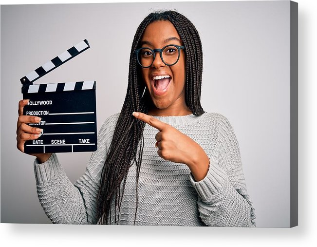 Director Acrylic Print featuring the photograph Young african american director girl filming a movie using clapboard over isolated background very happy pointing with hand and finger by AaronAmat