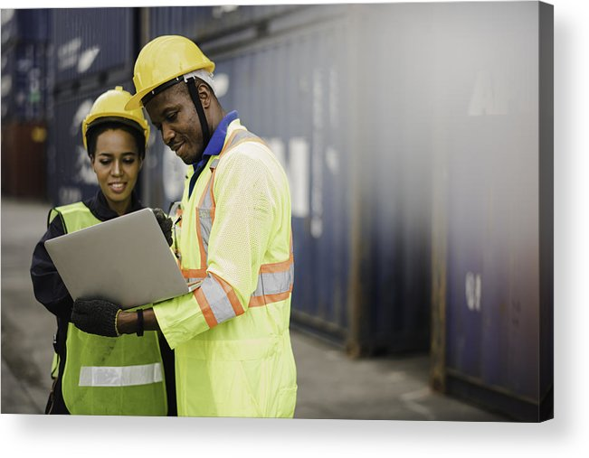 Working Acrylic Print featuring the photograph Young African american men and woman worker Check and control loading freight Containers by use computer laptop at commercial shipping dock felling happy. Cargo freight ship import export concept by Niphon Khiawprommas