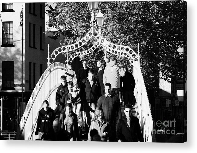 Dublin Acrylic Print featuring the photograph People Crossing The Hapenny Ha Penny Bridge Over The River Liffey In Dublin At A Busy Time by Joe Fox
