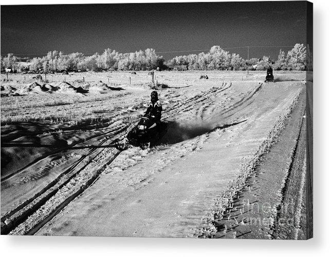 Man Acrylic Print featuring the photograph two men on snowmobiles crossing frozen fields in rural Forget Saskatchewan Canada by Joe Fox