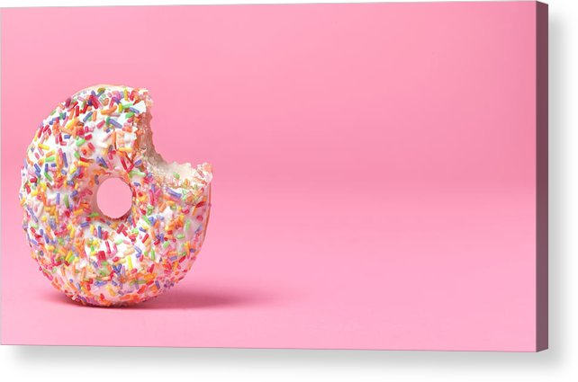 Unhealthy Eating Acrylic Print featuring the photograph Doughnut On Pink With Bite Out by Peter Dazeley