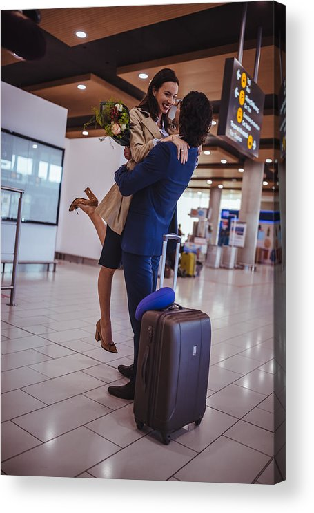 Young Men Acrylic Print featuring the photograph Excited Young Man Welcoming Girlfriend With Flowers At Airport by Wundervisuals