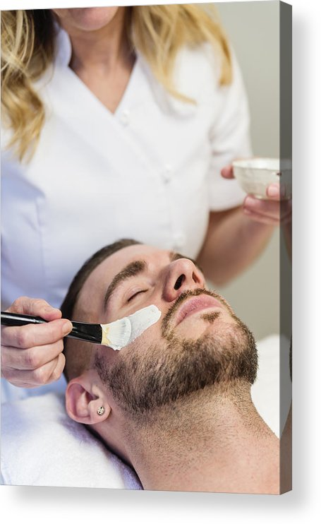 Young Men Acrylic Print featuring the photograph Young man receiving a facial treatment in beauty spa. by Martinedoucet