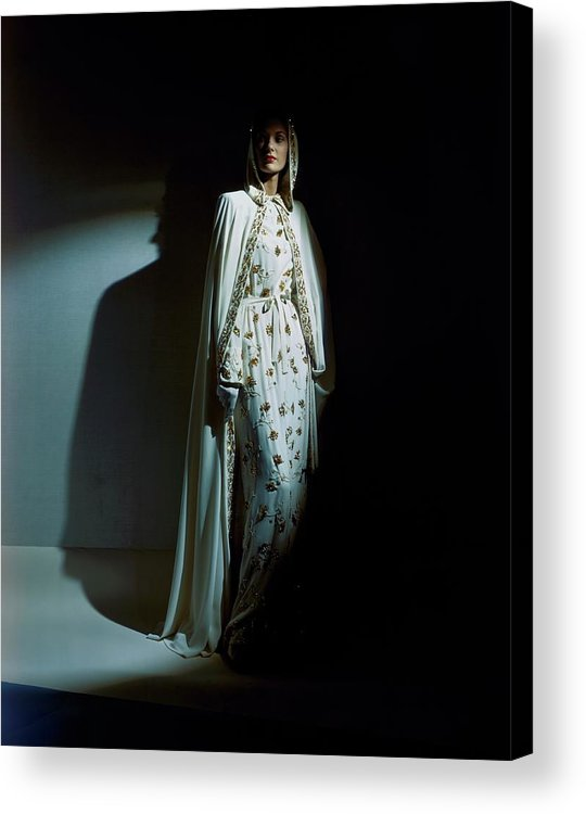 Fashion Acrylic Print featuring the photograph A Model Wearing A Hooded Ivory Cape Over An Ivory by Horst P. Horst