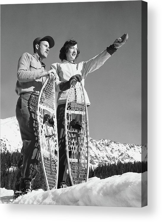 Heterosexual Couple Acrylic Print featuring the photograph Couple Holding Snowshoes, Woman Pointing by Stockbyte