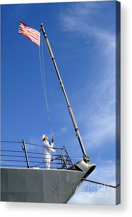 Pearl Harbor Acrylic Print featuring the photograph A Sailor Lowers The U.s. Navy Jack by Stocktrek Images