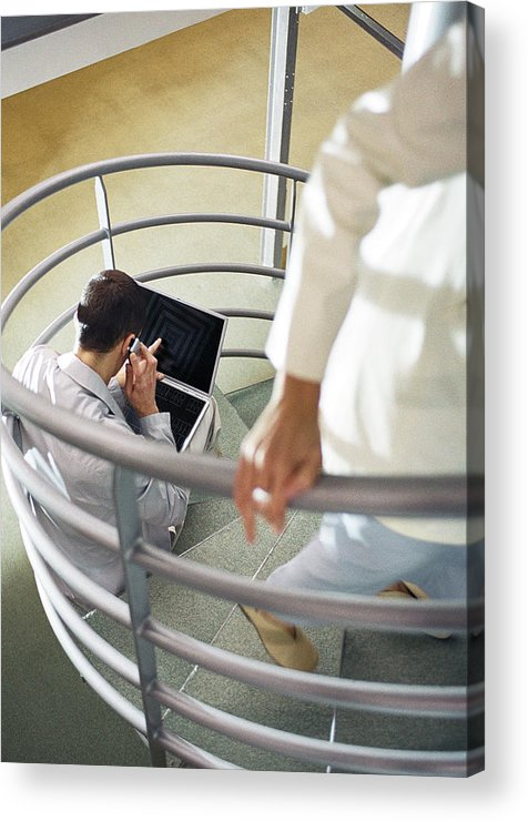 New Business Acrylic Print featuring the photograph Focus on man sitting on stairs with cell phone and laptop computer, person walking up stairs in foreground, blurred. by Coco Marlet