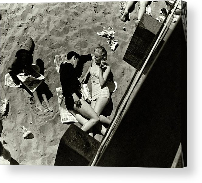 Swimwear Acrylic Print featuring the photograph A Young Couple Lying On A Beach by Lusha Nelson