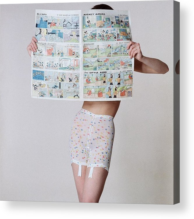 Fashion Acrylic Print featuring the photograph A Model Wearing A Girdle With A Comic by Louis Faurer