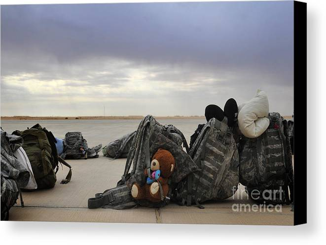 Iraq Canvas Print featuring the photograph Soldiers Backpacks On The Flight Line by Stocktrek Images