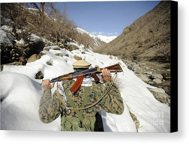 Terrain Canvas Print featuring the photograph A Mujahadeen Guard Walks With U.s by Stocktrek Images
