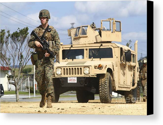 Motioning Canvas Print featuring the photograph A U.s. Marine Guides A Humvee by Stocktrek Images