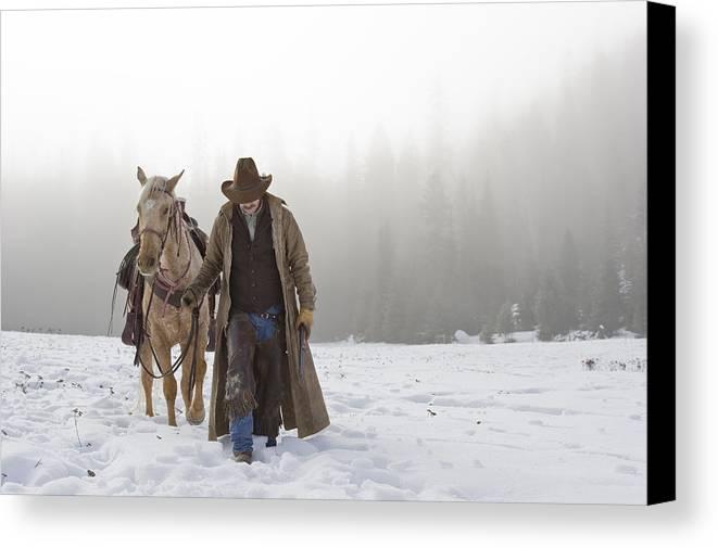 40-44 Years Canvas Print featuring the photograph Cowboy Walking His Horse And Holding A Shotgun by Thomas Kokta