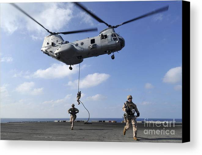 Fast Rope Canvas Print featuring the photograph Marines Fast Rope From A Ch-46e Sea by Stocktrek Images