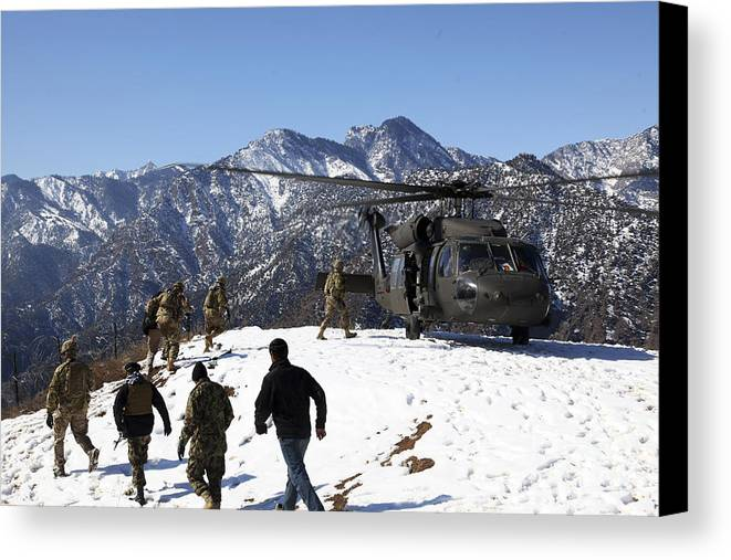 Us Army Canvas Print featuring the photograph Soldiers Board A U.s. Army Uh-60 Black by Stocktrek Images