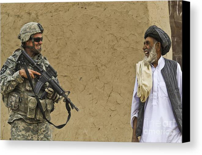 Afghan National Army Canvas Print featuring the photograph U.s. Army Specialist Talks To An Afghan by Stocktrek Images