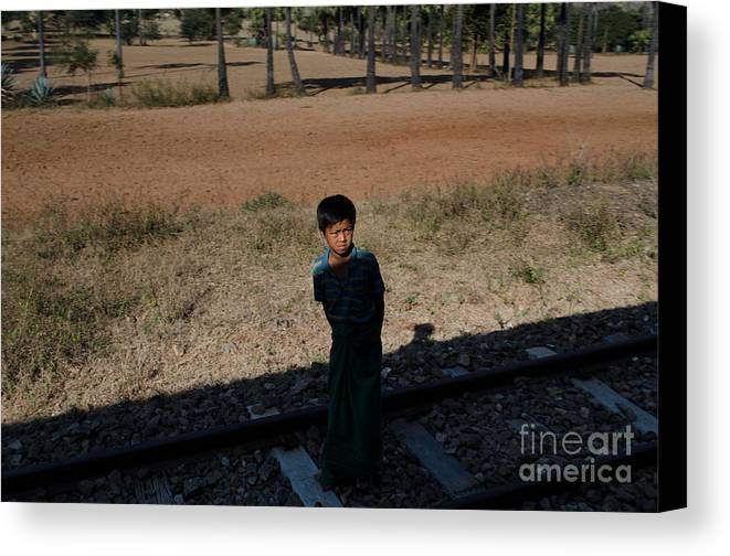 Asia Canvas Print featuring the photograph A Boy In Burma Looks Towards A Train From The Shadows by Jason Rosette