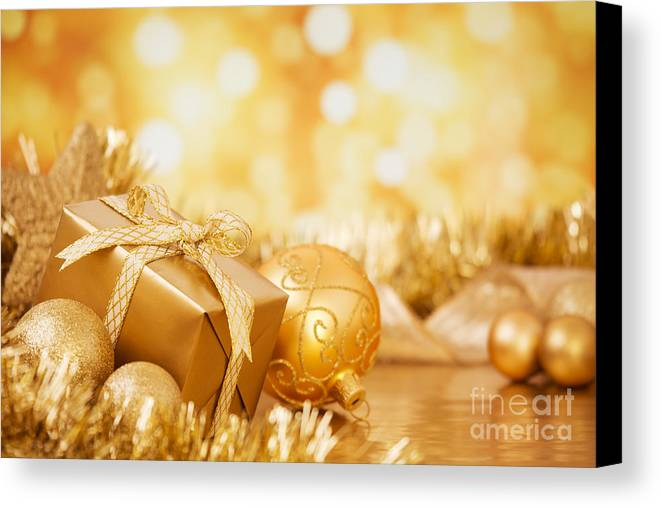 Baubles Canvas Print featuring the photograph Christmas Scene With Gold Baubles And Gift On A Gold Background by Sara Winter