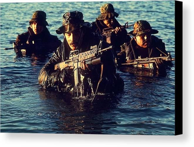 History Canvas Print featuring the photograph Us Navy Seal Team Emerges From Water by Everett