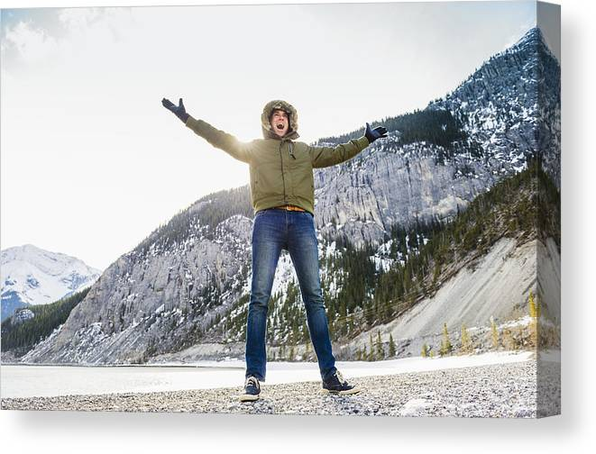 Young Men Canvas Print featuring the photograph Caucasian Man Cheering In Snowy Field by Jacobs Stock Photography Ltd