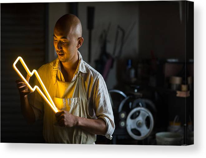 Working Canvas Print featuring the photograph Craftsmen Holding A Lightning Bolt Shaped Neon Light by Trevor Williams