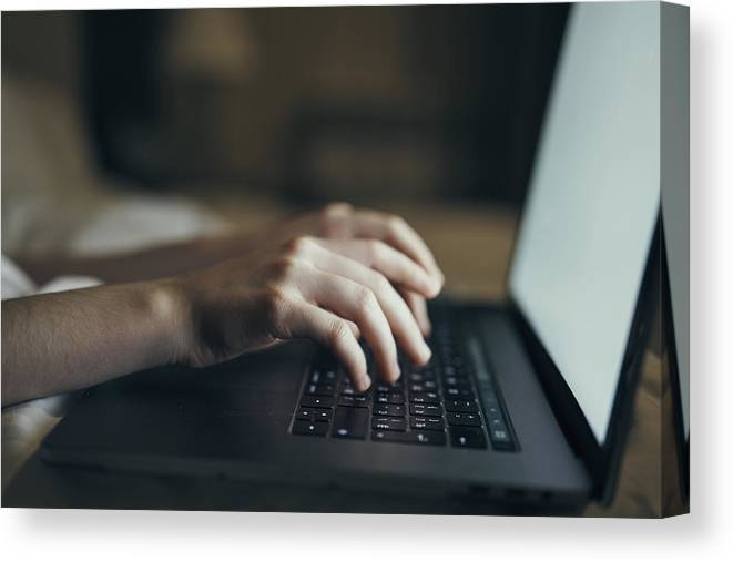 Hands Of Caucasian Woman Typing On Laptop In Bed Canvas Print