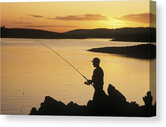 Atlantic Ocean Canvas Print featuring the photograph Silhouette Of A Fisherman Fishing On by The Irish Image Collection