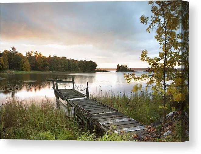 Sunrise Canvas Print featuring the photograph A Dock On A Lake At Sunrise Near Wawa by Susan Dykstra