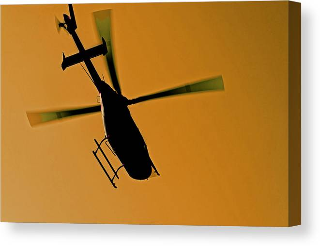 Interesting Canvas Print featuring the photograph Helicopter Silhouette In Flight by Kantilal Patel