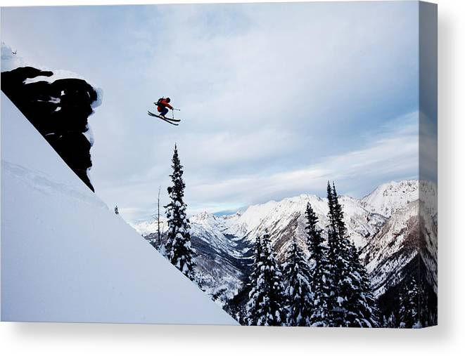 Skiing Canvas Print featuring the photograph A Athletic Skier Jumping Off A Cliff In by Patrick Orton