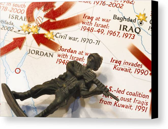 Aggression Canvas Print featuring the photograph Army Man Lying On Middle East Conflicts Map by Amy Cicconi