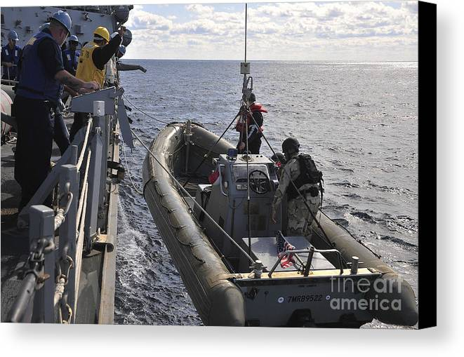 Uss Porter Canvas Print featuring the photograph Sailors Lift A Rigid-hull Inflatable by Stocktrek Images