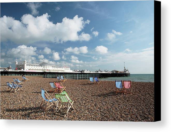 Red Canvas Print featuring the photograph Deckchairs On Brighton Beach by Neil Overy