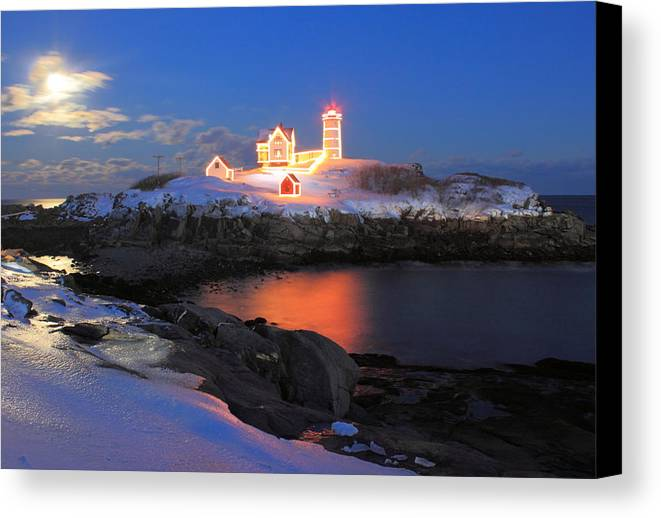 Nubble Lighthouse Canvas Print featuring the photograph Nubble Lighthouse Holiday Lights And Winter Moon by John Burk